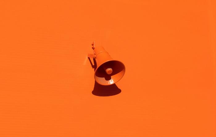 Megafono arancione su parete