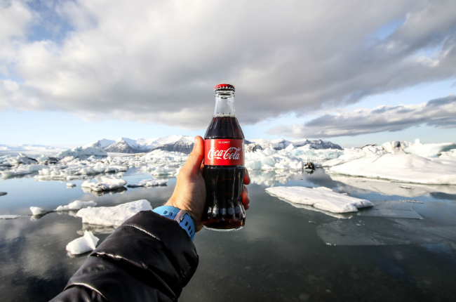 Glass bottle of coca cola being held in front of icebergs