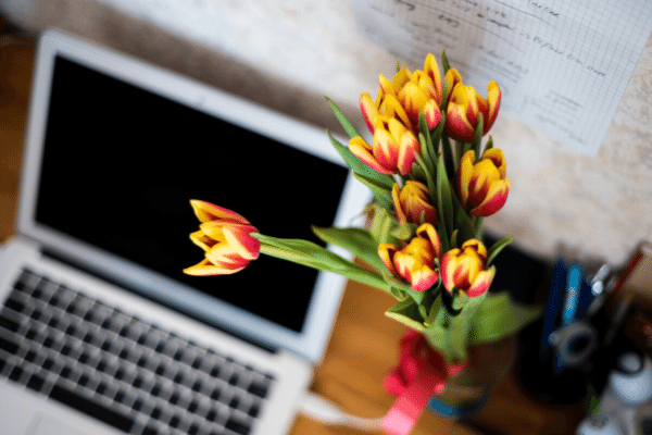 Flowers next to laptop, creating media list