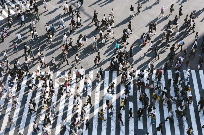 Crowd of people walking across a large, busy crosswalk