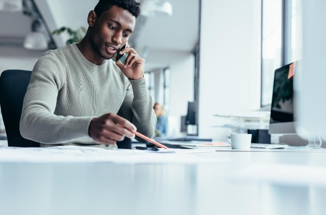 man working at his desk on the phone