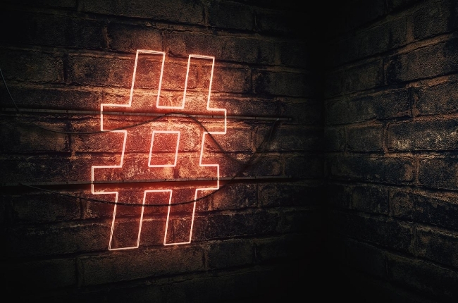 neon orange hashtag sign on a brick wall
