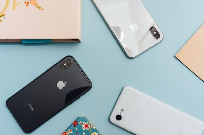 three iphones on a blue table