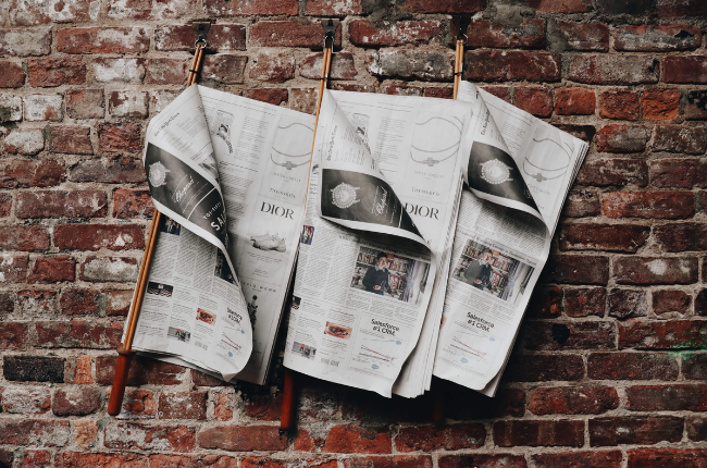 Newspapers on brick wall