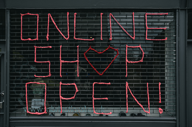 "Red sign ""Online Shop Open"" on gate"