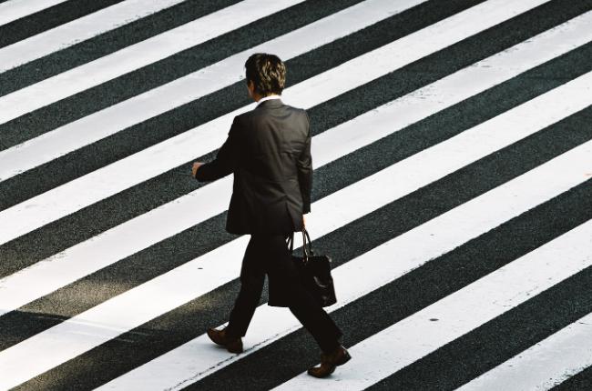 Person in suit walking through a crosswalk