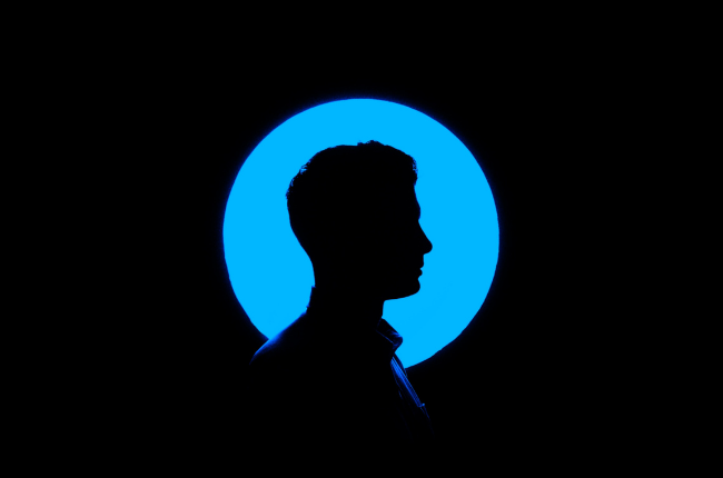 Silhouette of person against blue neon circle
