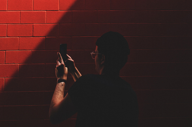 Person taking photo on phone against red brick wall